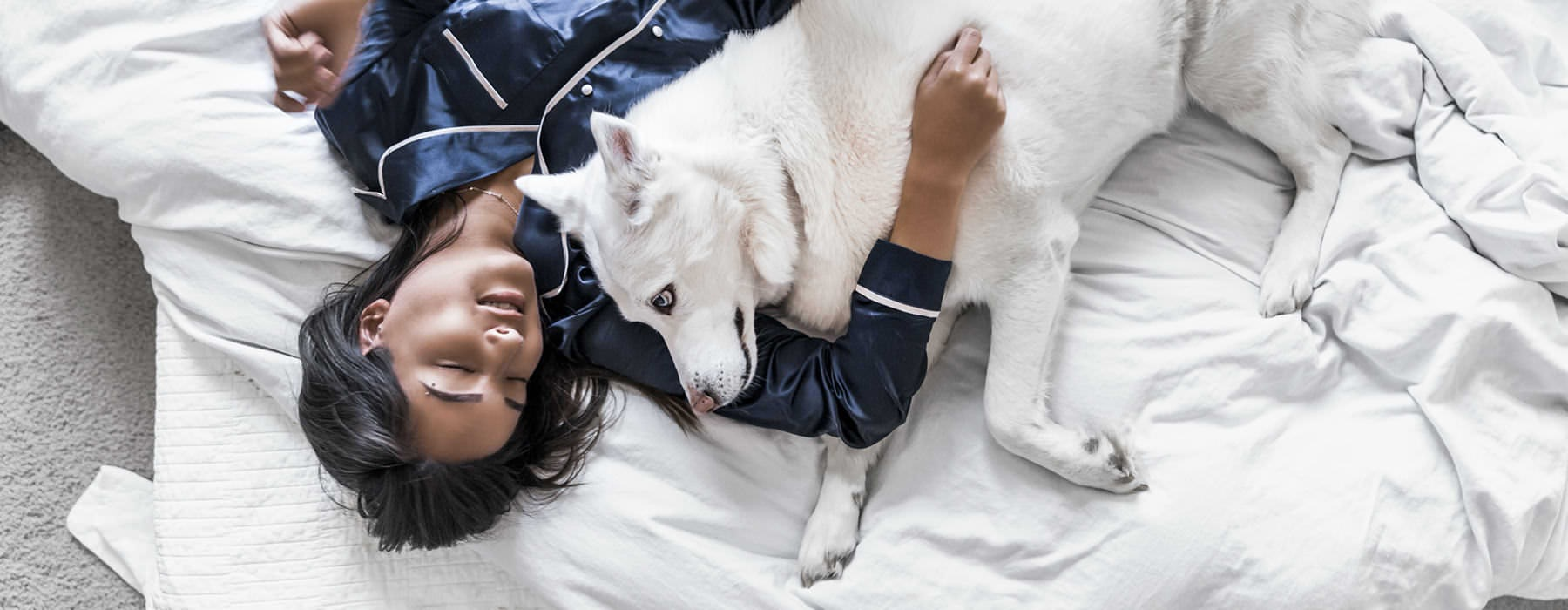 woman laying on a comforter with her white dog